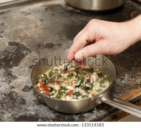 Chef is stirring risotto, copy space