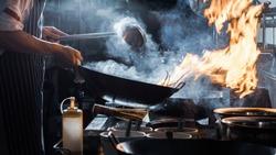 Chef is stirring vegetables in wok, vintage filter