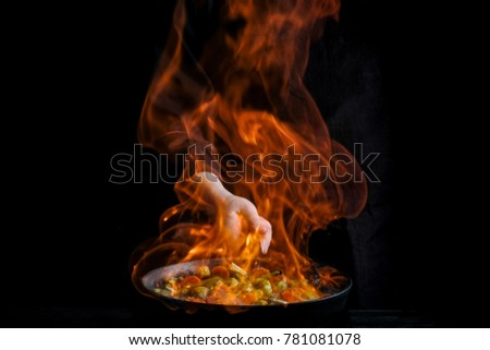 Chef is stirring vegetables in wok with fire. Dark black background. Stock photo ©