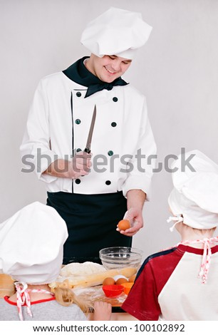 Chef is teaching kids to cook on the grey background
