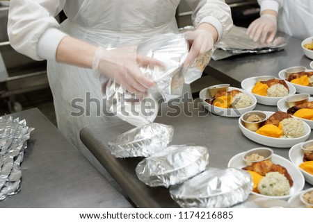 Chef is wrapping airline food in foil, professional kitchen