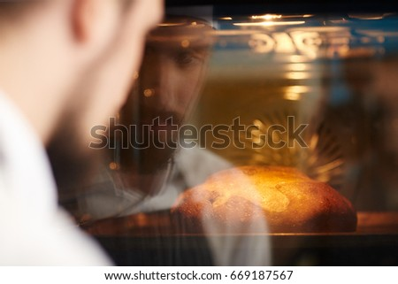 Chef looking at hot bread in oven