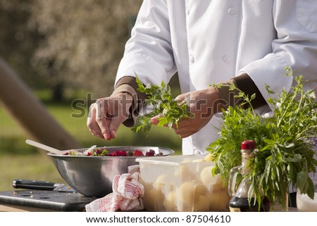 Chef makes beetroot salad with organic parsley. Outdoors. - stock photo