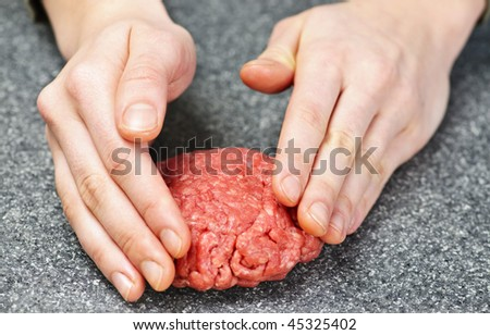 Chef making hamburger patty in kitchen with ground beef