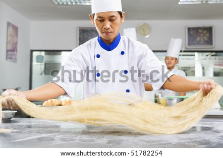 Chef making noodle in the kitchen of cooking school. ***PS : selective focus on the noodle with noticeable movement blur ***
