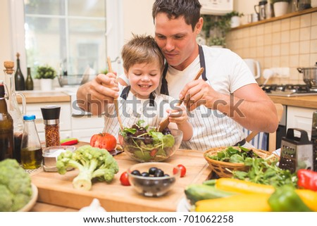 Chef man cooking on the kitchen with little son.