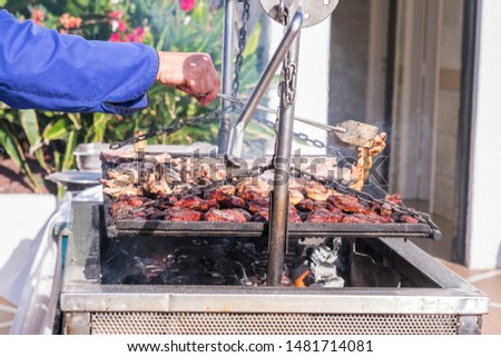 Chef man grill barbecue with fire and food meal - restaurant and home cooking concept - chef at work outdoor with fresh pork and cow