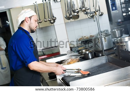 chef man in uniform frying a fish slice on grill in kitchen