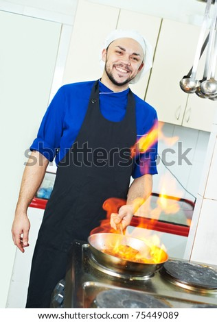 chef man in uniform making flambe meal with frying pan in kitchen