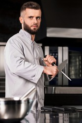 Chef man with knife at kitchen restaurant. Portrait of male cook sharp knife. Concentrated chef in uniform sharp knife at professional restaurant.