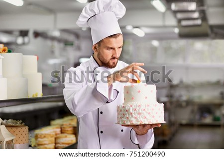 Chef pastry decorates cake in the kitchen. #751200490