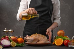 Chef pouring olive oil on a chicken preparing it for baking. Freezing in motion. Against the background of vegetables, fruits and ingredients