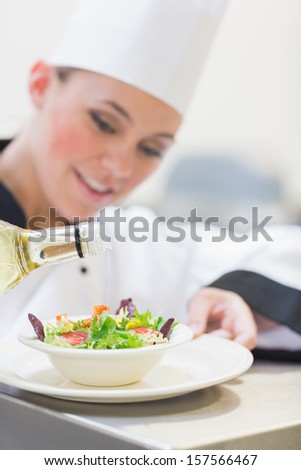Chef pouring olive oil over salad in kitchen