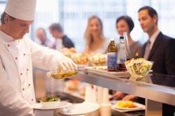 Chef pouring olive oil salad dressing on salad in work cafeteria