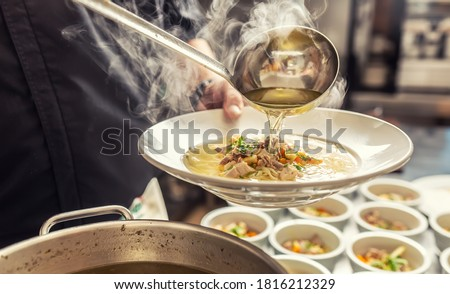 Chef pours broth into a chicken soup with noodles, meat and vegetable. Сток-фото ©