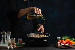 Chef pours olive oil for frying meat with mushrooms for cooking, on the background of vegetables, freezing in motion, culinary recipes, menus, restaurant business, home recipes