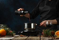 Chef pours red wine into pan for preparing mulled wine on rustic wooden table with festive composition background. Backstage of cooking hot drink with fragrant spices. Dark blue background.