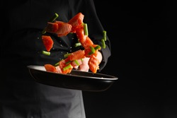 Chef prepares pieces of salmon or trout fillet with green beans in a pan, on a black background for design, recipe book, menu, restaurant or hotel sign, cooking, gastronomy