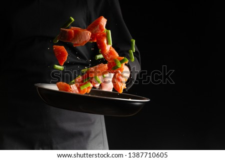 Chef prepares pieces of salmon or trout fillet with green beans in a pan, on a black background for design, recipe book, menu, restaurant or hotel sign, cooking, gastronomy #1387710605