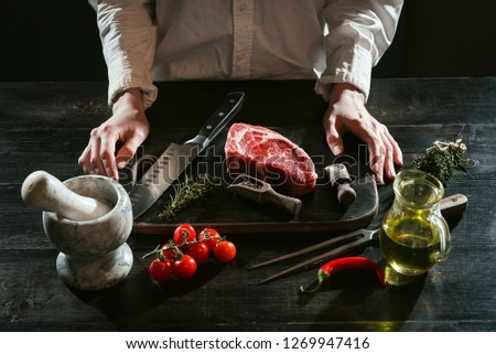 chef prepares rib-eye steak from a piece of fresh marbled beef