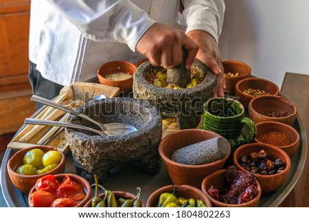 Chef preparing a traditional Pasilla Chili Sauce with all the ingredients, Oaxaca, Mexico. Focus on mortar, blur motion. Stockfoto ©