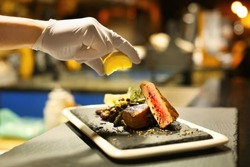 Chef preparing grilled tuna for serving in restaurant