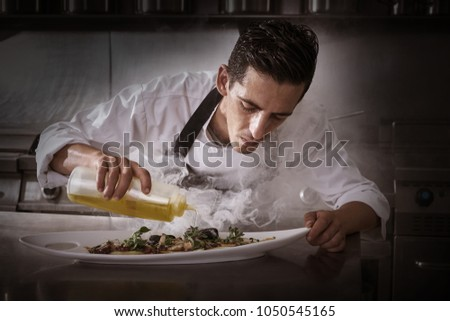 Chef preparing octopus recipe in kitchen with smoke and oil #1050545165
