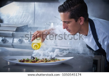 Chef preparing octopus recipe in kitchen with smoke and oil #1050545174