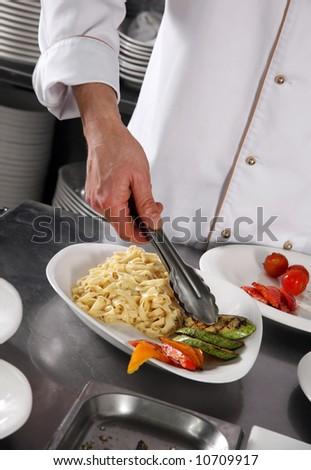 Chef preparing pasta on professional kitchen in restaurant
