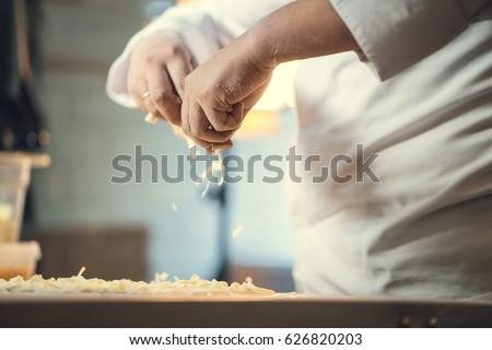 Chef preparing pizza in kitchen