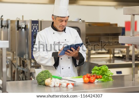 Chef preparing recipe with digital tablet in the kitchen