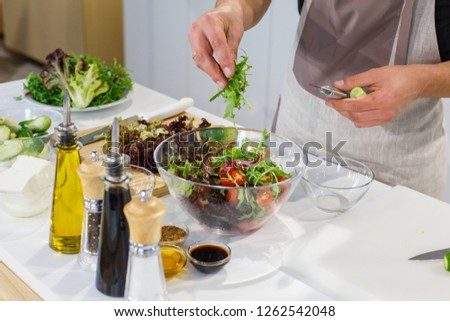 Chef preparing salad from fresh vegetables, greenery and sauce on white table