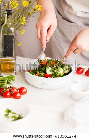 Chef preparing spring salad. Cucumber, spring onion, tomatoes salad bowl.  #613561274