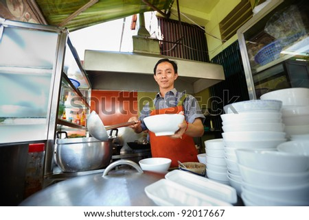 Chef preparing traditional Asian street food and working in the restaurant kitchen. Horizontal shape, front view