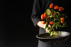 Chef preparing vegetables in a pan, Asian cuisine, on a black background for design, recipe book, menu, restaurant or hotel sign, cooking, gastronomy
