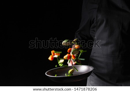 Chef preparing vegetables in a pan, Asian cuisine, on a black background for design, recipe book, menu, restaurant or hotel sign, cooking, gastronomy #1471878206