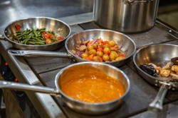Chef preparing vegetables on frying pan in the professional kitchen.