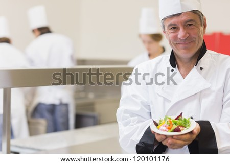 Chef presenting his salad in the kitchen
