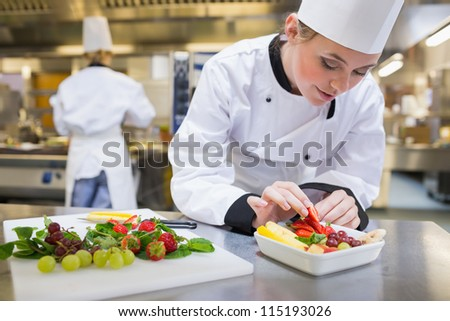 Chef putting a strawberry in the fruit salad in the kitchen