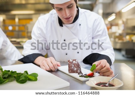 Chef putting mint leaf with his dessert in the kitchen - stock photo