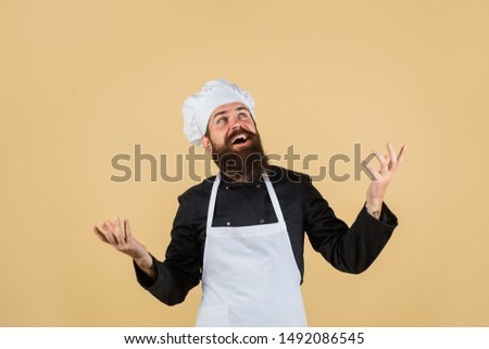 Chef ready to cooking new dish. Bearded man in kitchen apron. Male cook in chef hat. Professional cook man. Chief cook and professional culinary. Chef, cook or baker man. Bearded man chef in uniform.