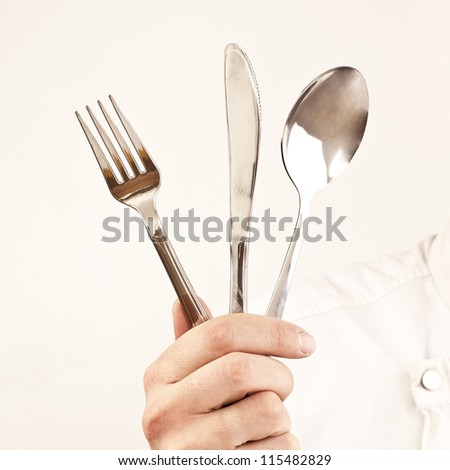 chef's hand with a knife, spoon and fork on a gray background - stock photo