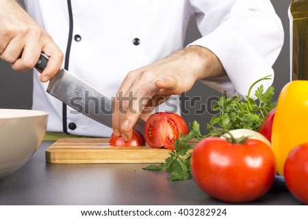 Chef's hands cutting red fresh tomato on a wooden board