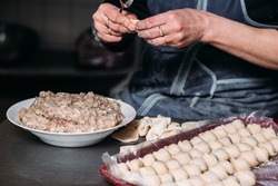 Chef's hands make dumplings from dough and ground beef