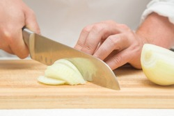 Chef's hands with knife cutting the onion on the wooden board. Preparation for cooking. Healthy eating and lifestyle.