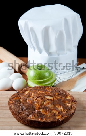 Chef's hat or toque with an apple pie and kitchen utensils, over dark background