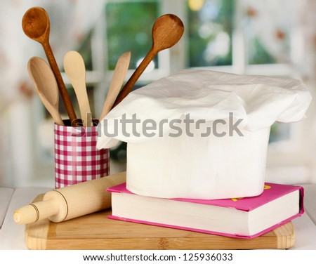 Chef's hat with battledore and cook book on board on wooden table on window background