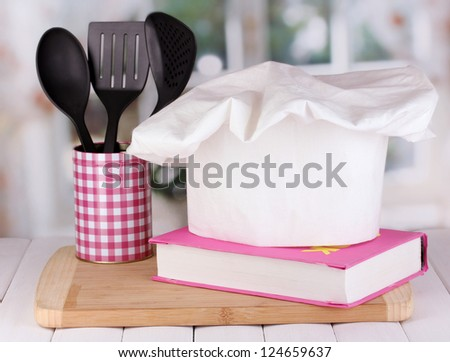 Chef's hat with spoons and cook book on board on wooden table on window background