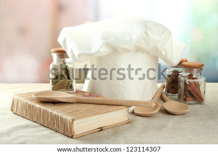 Chef's hat with spoons on table in kitchen