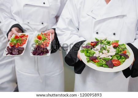Chef's holding out their salads in kitchen